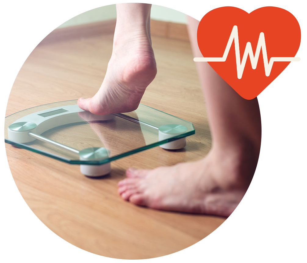 Two bare feet with one stepping on a weight scale