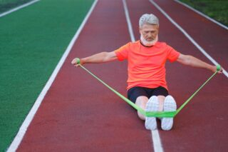 elderly man exercises with resistance band for weight loss program